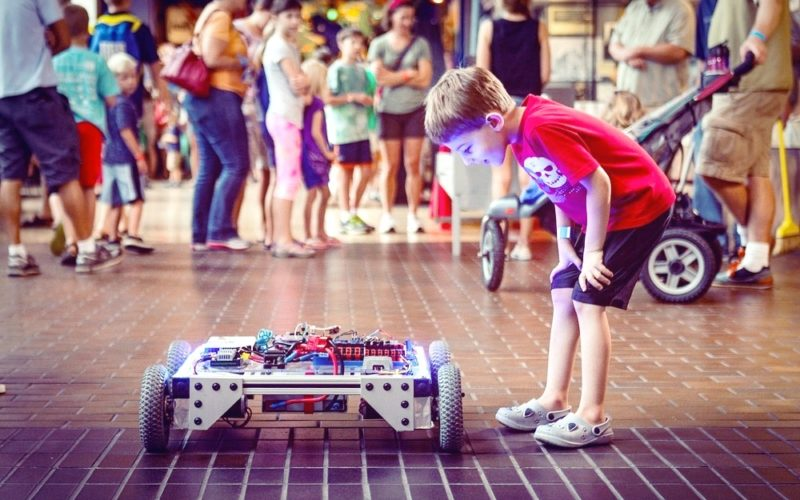 A boy is looking at a maker faire project during Makerfair festival
